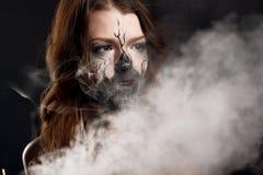 La fille avec composent et les nuages électroniques de fabrication des cigarettes Photographie stock
