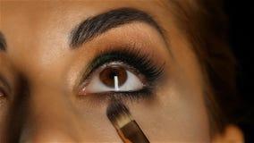 La fille avec composent la recherche, brosse de visagiste ajuste son maquillage Fin vers le haut Mouvement lent banque de vidéos