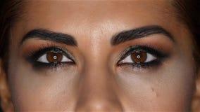 La fille avec composent, son visage composé écrème et de beaux yeux Fin vers le haut Mouvement lent banque de vidéos
