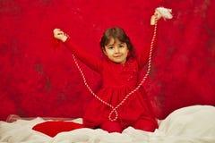La fille avec de la ficelle rouge et blanche d'iÈ™or de› de MărÈ Photographie stock libre de droits