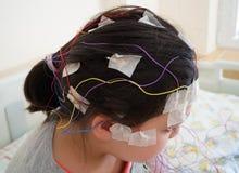 La fille avec des électrodes d'EEG a attaché à sa tête pour l'examen médical Photographie stock