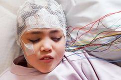 La fille avec des électrodes d'EEG a attaché à sa tête pour l'examen médical Images libres de droits