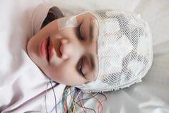 La fille avec des électrodes d'EEG a attaché à sa tête pour l'examen médical Photo libre de droits