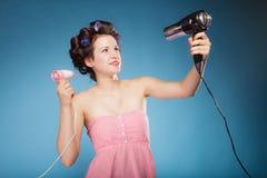La fille avec des bigoudis dans les cheveux tient des hairdreyers Image stock