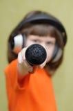 La fille avec des bouts droits d'écouteurs expédient le microphone Photographie stock libre de droits