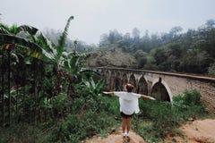 La fille avec des bras ouvrent des positions contre le pont photo libre de droits