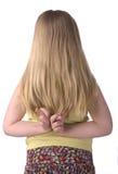 La fille avec des doigts a croisé derrière en arrière Photos stock