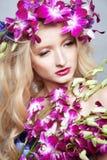 La fille avec des fleurs. Photo stock