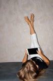La fille avec des jambes se lèvent et marquent sur tablette dans des mains Images libres de droits