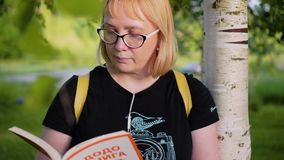 La fille avec des verres est en parc d'été sous un arbre se penchant sur lui et lisant un livre Elle regarde le livre très soigne banque de vidéos