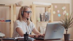 La fille avec des verres et l'aspect caucasien de chemise blanche travaille dans le bureau, en même temps parlant sur le casque d banque de vidéos