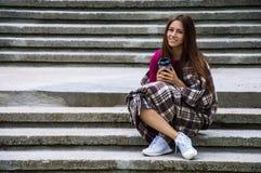 La fille avec du charme s'assied sur les escaliers enveloppés dans une couverture Images stock