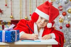 La fille avec enthousiasme dessine une carte de Noël Image libre de droits