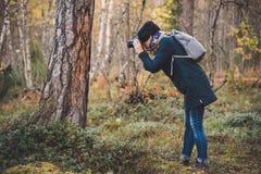 La fille avec l'appareil-photo photographie l'écorce d'arbre dans le bois photo libre de droits