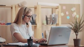 La fille avec l'aspect caucasien en verre, se reposant à un casque d'ordinateur avec le microphone à distance et conseille des pe banque de vidéos
