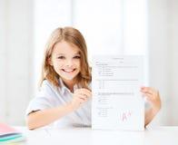 La fille avec l'essai et l'A évaluent à l'école Photographie stock libre de droits