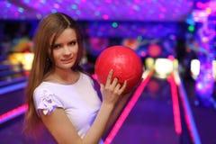 La fille avec la bille reste dans le club de bowling Photo libre de droits