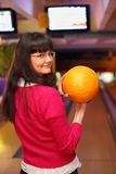 La fille avec la bille reste dans le club de bowling Photo stock