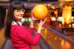 La fille avec la bille reste dans le club de bowling Image stock