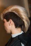 La fille avec la coupe de cheveux courte dans le plan rapproché de salon de coiffure Image libre de droits