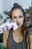 La fille avec la fleur d'orchidée est très triste Images stock