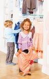 La fille avec la robe et le garçon derrière choisit des vêtements Photos libres de droits