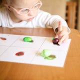 La fille avec la trisomie 21 est impliquée en assortissant des légumes Photographie stock libre de droits