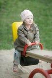 La fille avec la trisomie 21 ont l'équitation d'amusement sur une oscillation Photos stock