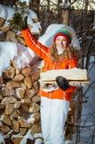 La fille avec le bois de chauffage pendant l'hiver Photographie stock libre de droits