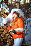 La fille avec le bois de chauffage pendant l'hiver Images stock
