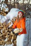 La fille avec le bois de chauffage pendant l'hiver Photographie stock