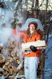 La fille avec le bois de chauffage pendant l'hiver Image stock
