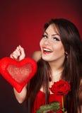 La fille avec le coeur et s'est levée sur le fond rouge Photos libres de droits