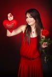 La fille avec le coeur et s'est levée sur le fond rouge. Photo stock