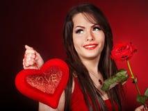 La fille avec le coeur et s'est levée sur le fond rouge. Image stock