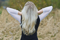 La fille avec le long dos de cheveu blond est Images stock