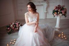La fille avec le maquillage dans une robe de mariage rose s'assied dans une belle salle entourée par des fleurs et des bougies Images stock