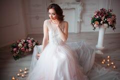 La fille avec le maquillage dans une robe de mariage rose s'assied dans une belle salle entourée par des fleurs et des bougies Image stock