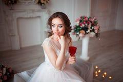 La fille avec le maquillage dans une robe de mariage rose s'assied dans une belle salle entourée par des fleurs et des bougies La Photographie stock