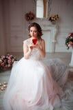 La fille avec le maquillage dans une robe de mariage rose s'assied dans une belle salle entourée par des fleurs et des bougies La Photo libre de droits