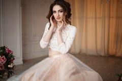 La fille avec le maquillage dans une robe de mariage s'assied dans une belle salle Images libres de droits