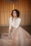 La fille avec le maquillage dans une robe de mariage s'assied dans une belle salle Photo libre de droits