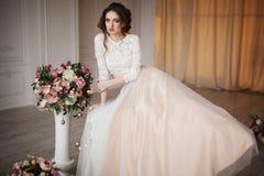La fille avec le maquillage dans une robe de mariage s'assied dans une belle salle Photos libres de droits