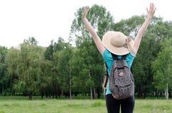 La fille avec le sac à dos et le chapeau recule avec des mains contre la forêt Images libres de droits