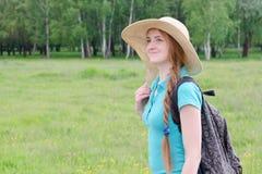 La fille avec le sac à dos et le chapeau se tient contre la forêt d'été Images libres de droits