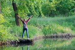 La fille avec le sac à dos recule avec des mains contre la forêt et le lac Photos libres de droits