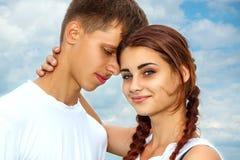 La fille avec le type se tenant en s'étreignant sur le fond de ciel photos libres de droits