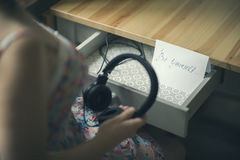 La fille avec les écouteurs et le message soit vous-même L'inscription sur le de papier soit vous-même Image stock