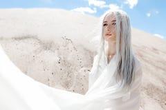 La fille avec les cheveux blancs parmi les montagnes de sable image stock