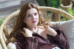 La fille avec les cheveux bouclés rouges s'assied dans la chaise en osier image stock